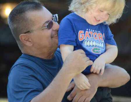 Vinny Esposito of EXIT Riverside Realty in Dunnellon holds his grandson, Luthor, 2, as they watch the Dunnellon Duck Race