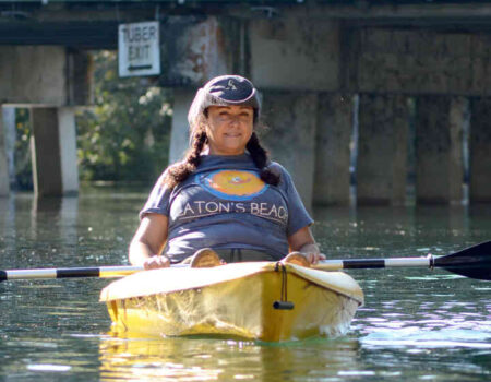 At the Dunnellon Duck Race on September 25, Jacqueline Rodriguez from Dunnellon Dry Cleaners watches from her kayak