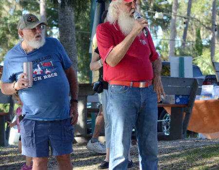 AS Keith Carson of the Believe in Santa Foundation reports on the race, Ruff Pennington of American Legion Post 58 watches